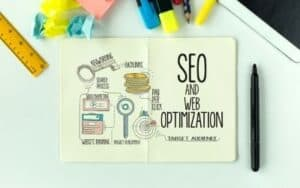 notebook with pictures related to seo and website optimization, highlighters, and crumpled pieces of paper