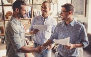 partners in a partnership agreement 3 men wearing different blue shirts
