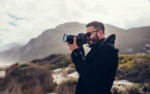 photographer wearing black jacket with hills behind